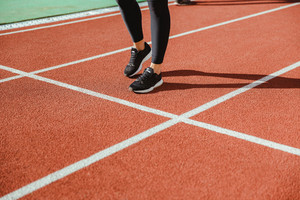 Closeup portrait of female runner legs at stadium