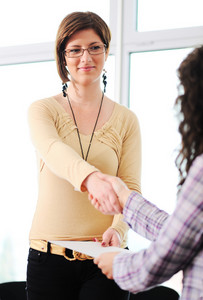 Closing a deal with a female handshake. Signed contract in the hand between women.