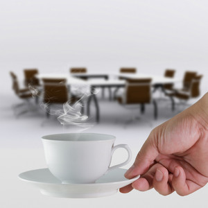 Coffee Cup In Hand Business And Meeting Room Background