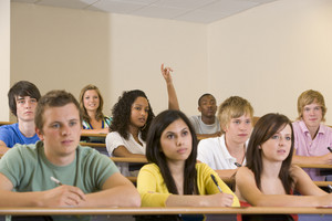 College student with hand raised in university lecture hall