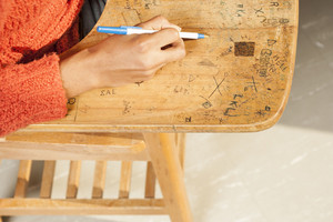 College student writing on desk