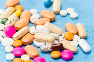 Color medicament pills spilled capsules on medical blue cloth