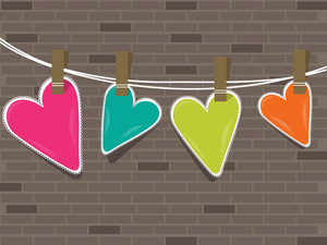 Colorful Hearts Hanging On A Line Against Wall .