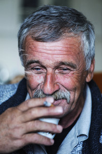 Common elderly man with mustache smoking cigarette and drinking coffee