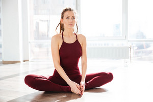 Concentrated attractive young woman stretching and doing yoga in studio