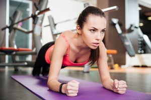 Concentrated beautiful young sportswoman doing plank exercise on mat in gym