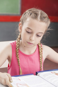 Concentrated girl reading at school