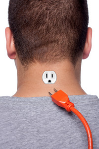 Conceptual image of a young man with an electrical socket on the back of his neck with the power plug disconnected.
