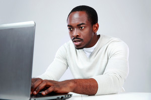 Concetrated african man using laptop on gray background