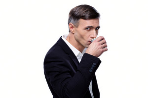 Confident businessman drinking coffee over white background