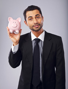 Confident businessman holding a piggy bank