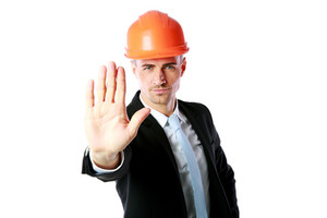 Confident businessman in helmet showing stop gesture over white background