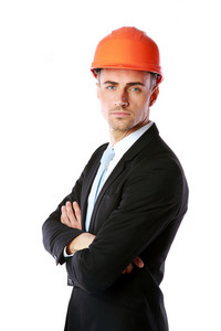 Confident businessman in helmet standing with arms folded over white background