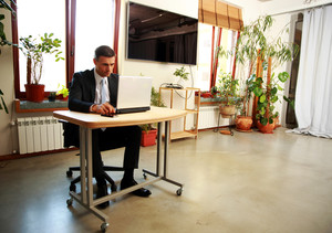 Confident businessman sitting at the table and using laptop in office