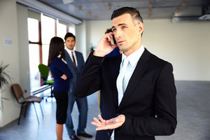 Confident businessman talking on the phone in front of colleagues
