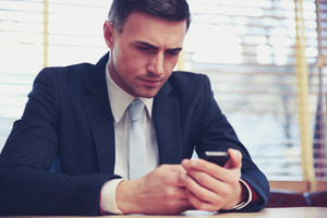 Confident businessman using smartphone at office