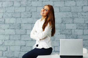 Confident happy businesswoman sitting at the table with arms folded