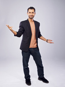 Confident man standing in a studio doing hand gesture