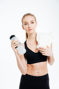 Confident pretty young sportswoman holding bottle of water and white towel