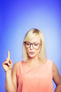 Confident woman pointing her finger up while thinking of a solution to her problem