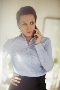 Confident young businesswoman talking business on the phone. Caucasian female using mobile phone looking away.