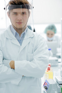 Confident young doctor with mask and folded hands in hospital laboratory