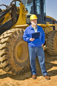 Construction Worker With Clipboard and Earthmoving Equipment