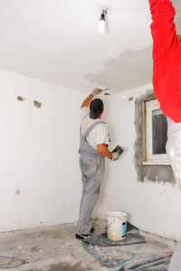 Construction workers painting walls