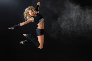 Contemporary dancer woman jumping dance on black background
