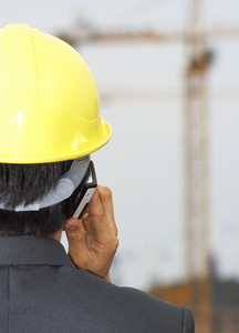 Contractor On The Phone Inspecting A Building Site