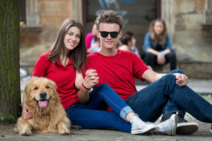 Cool young couple posing with dog sitting on the street