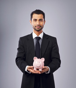 Corporate man holding a coin bank