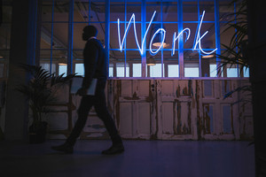 Corridor of a modern office with a neon work sign and executive walking by.