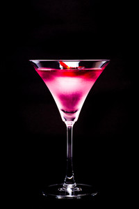 Cosmopolitan cocktail with rose in top of a black background