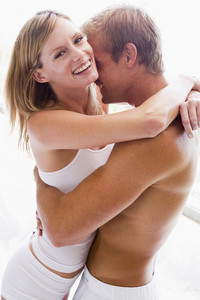 Couple bedroom embracing and smiling