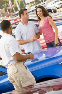 Couple discussing new car with salesman on lot