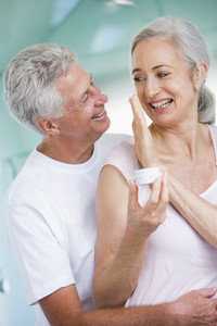 Couple embracing at a spa holding cream and smiling
