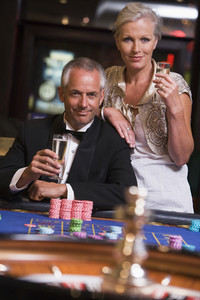 Couple gambling at roulette table in casino