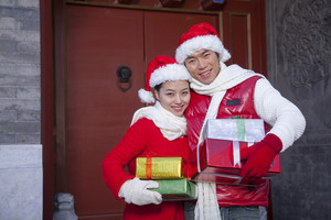 Couple holding gifts dressed in holiday attire