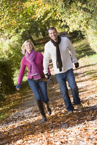 Couple holding hands on walk through autumn woods