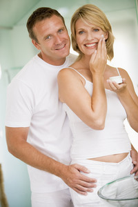 Couple in bathroom with face cream smiling