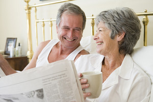 Couple in bedroom with coffee and newspapers smiling