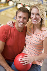Couple in bowling alley holding ball and smiling