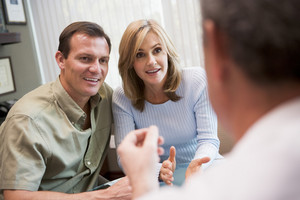 Couple in consultation at IVF clinic talking to physician