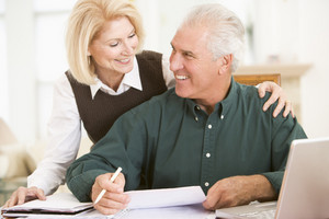 Couple in dining room with laptop and paperwork smiling