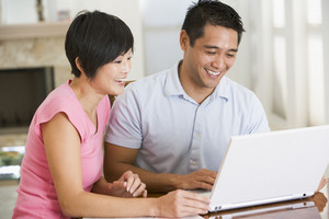 Couple in dining room with laptop smiling