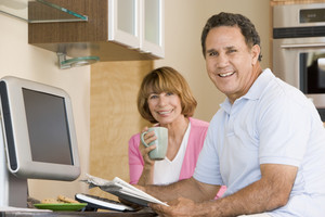 Couple in kitchen with coffee and newspaper smiling
