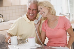 Couple in kitchen with coffee using telephone together and smiling