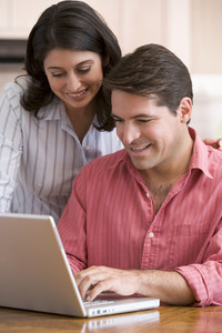 Couple in kitchen with paperwork using laptop smiling
