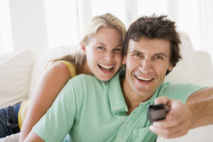 Couple in living room holding remote control smiling